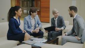Empresaria con la tableta digital que habla con los colegas del varón y del femalebusiness que se sientan en el sofá en oficina m