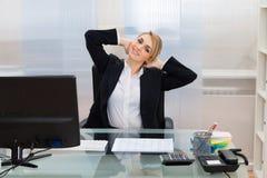 Empresaria con las manos detrás de la cabeza en el escritorio imagenes de archivo