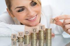 Empresaria con los bloques del presupuesto en monedas apiladas Foto de archivo