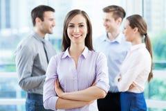 Empresaria con los compañeros de trabajo en fondo imagen de archivo libre de regalías