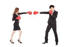 Empresaria con los guantes de boxeo que tienen una lucha con el hombre Imágenes de archivo libres de regalías
