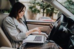 Empresaria con un ordenador portátil en su coche en la calle fotos de archivo