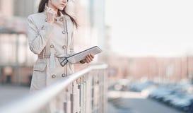 Empresaria con una tableta digital, coloc?ndose en la terraza cerca del centro de negocios foto de archivo libre de regalías