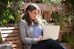 Empresaria concentrada que trabaja con el ordenador portátil en el banco Imagen de archivo libre de regalías