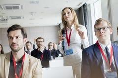Empresaria confiada que gesticula mientras que sostiene el micrófono durante seminario imagen de archivo