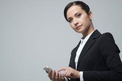 Empresaria confiada sonriente que usa el teléfono móvil de la pantalla táctil Foto de archivo libre de regalías