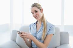 Empresaria contenta hermosa que manda un SMS con su smartphone que se sienta en el sofá Foto de archivo libre de regalías