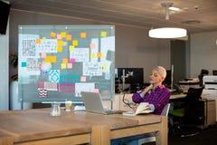 Empresaria creativa cansada que se sienta en el escritorio imagen de archivo libre de regalías