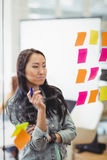Empresaria creativa que mira notas pegajosas coloreadas multi Imágenes de archivo libres de regalías