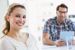 Empresaria creativa sonriente con su colega detrás Foto de archivo libre de regalías