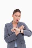 Empresaria dada una sacudida eléctrica que mira su reloj Imagen de archivo libre de regalías