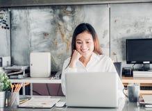 Empresaria de Asia que mira el ordenador portátil y la cara sonriente a fotografía de archivo