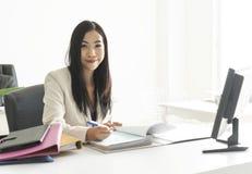 Empresaria de Asia que trabaja en el escritorio en su oficina fotos de archivo libres de regalías