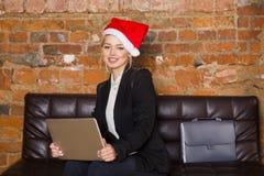Empresaria de la muchacha de Papá Noel con el cuaderno y el ordenador portátil en la oficina del desván en el sofá de cuero en tr Fotos de archivo