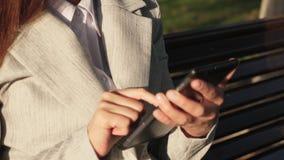 Empresaria de la mujer joven con el correo electrónico de los controles de los vidrios en la tableta en parque en un banco metrajes