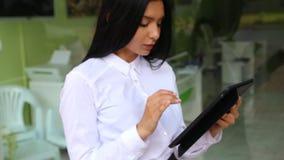 Empresaria de Latina que sostiene la tableta en manos, blusa blanca que lleva metrajes