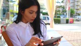 Empresaria de Latina que sostiene la tableta en manos, blusa blanca que lleva almacen de video