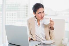 Empresaria de pensamiento que sostiene la taza mientras que trabaja en el ordenador portátil Fotos de archivo