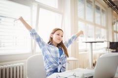 Empresaria de Succesfull con los brazos extendidos mientras que se sienta en la oficina Fotografía de archivo libre de regalías