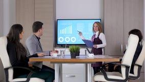 Empresaria delante de la pantalla grande TV que presenta datos animados y cartas almacen de video