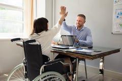 Empresaria discapacitada Giving High Five a su socio foto de archivo libre de regalías
