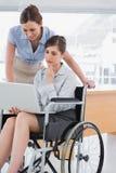 Empresaria discapacitada que mira el ordenador portátil con su colega Foto de archivo libre de regalías