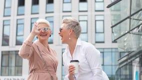Empresaria dos que camina en la calle cerca del edificio mujer de negocios que viene acompañada de la tableta almacen de metraje de vídeo