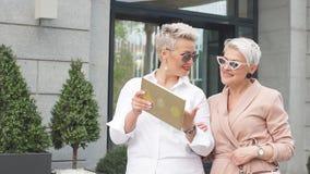 Empresaria dos que camina en la calle cerca del edificio mujer de negocios que viene acompañada de la tableta metrajes