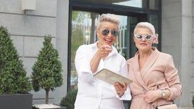 Empresaria dos que camina en la calle cerca del edificio mujer de negocios que viene acompañada de la tableta almacen de video