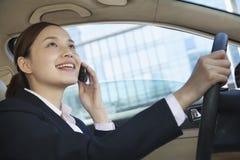 Empresaria Driving y en el teléfono en Pekín foto de archivo