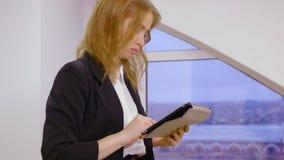 Empresaria ejecutiva en el traje negro que trabaja en la tableta, grúa tirada de las piernas almacen de metraje de vídeo
