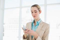 Empresaria elegante concentrada que manda un SMS con su smartphone Imágenes de archivo libres de regalías