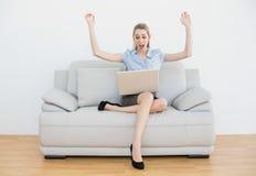 Empresaria elegante extremadamente que anima que se sienta en su sofá Imagen de archivo libre de regalías