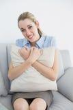 Empresaria elegante linda que sostiene una almohada que se sienta en el sofá Imagen de archivo libre de regalías