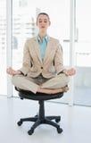 Empresaria elegante pacífica que se sienta en la posición de loto respecto a silla de eslabón giratorio Imagen de archivo