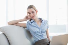 Empresaria elegante que se sienta en el sofá que sostiene su cuaderno Fotografía de archivo libre de regalías