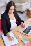 Empresaria embarazada que hace notas mientras que trabaja en el ordenador portátil fotografía de archivo