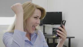 Empresaria emocionada acertada que mira grandes noticias en el smartphone que anima y que celebra su triunfo que hace sí gesto - almacen de metraje de vídeo