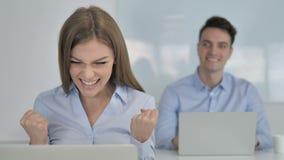 Empresaria emocionada Celebrating Success mientras que trabaja en el ordenador portátil metrajes