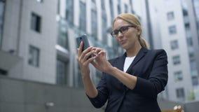Empresaria emocionada con el app conveniente en smartphone, organizador electrónico almacen de metraje de vídeo