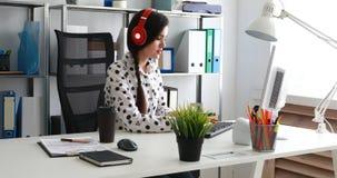 Empresaria en auriculares rojos usando el ordenador portátil en oficina moderna metrajes