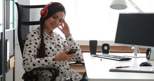 Empresaria en auriculares rojos usando smartphone en oficina moderna almacen de video