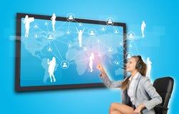 Empresaria en auriculares usando la pantalla táctil Foto de archivo libre de regalías