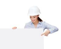 Empresaria en casco que señala el finger al tablero Foto de archivo libre de regalías