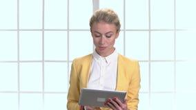 Empresaria en chaqueta amarilla con la tableta almacen de video