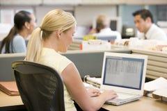 Empresaria en cubículo usando la computadora portátil fotografía de archivo libre de regalías