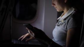 Empresaria en el avión de pasajeros que manda un SMS en smartphone en la noche almacen de metraje de vídeo
