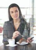 Empresaria en el café de la oficina que tiene torta Imagen de archivo