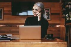 Empresaria en el café que hace una llamada de teléfono fotografía de archivo libre de regalías
