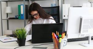 Empresaria en el funcionamiento de vidrios negro en el ordenador portátil en oficina moderna almacen de metraje de vídeo